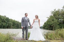 bride and groom holding hands in front of lake