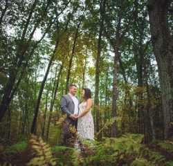 bride and groom in wood smiling at each other
