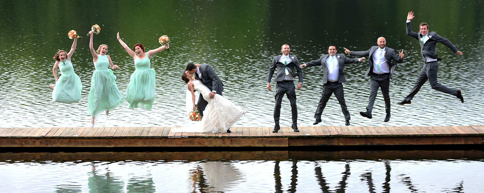 groom dipping bride and kissing on dock