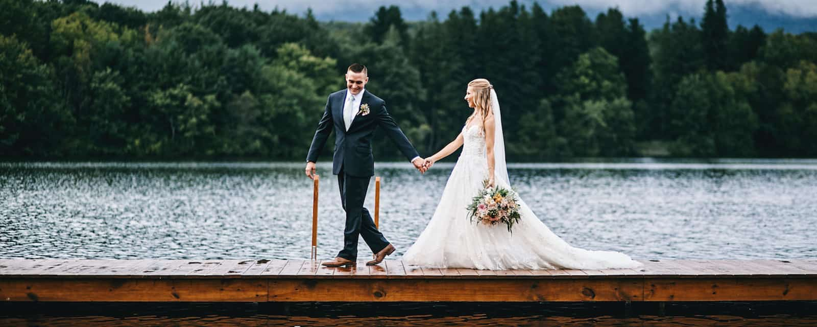 bride and groom holding hands at lake